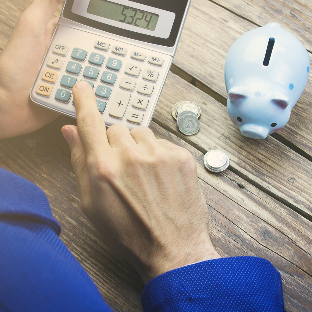 Person typing on a calculator next to a piggy bank.