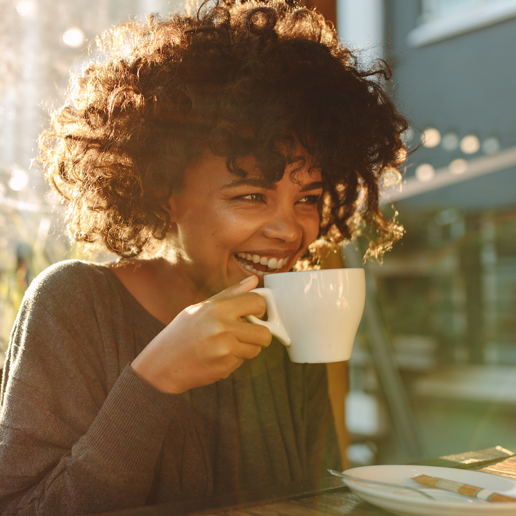 Woman laughing and drinking coffee.
