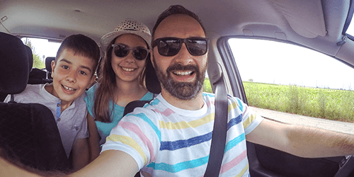 Man and kids taking a selfie while driving.