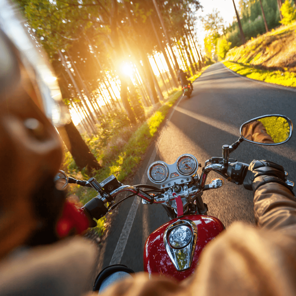 Motorcycle driving down a street at sunset.