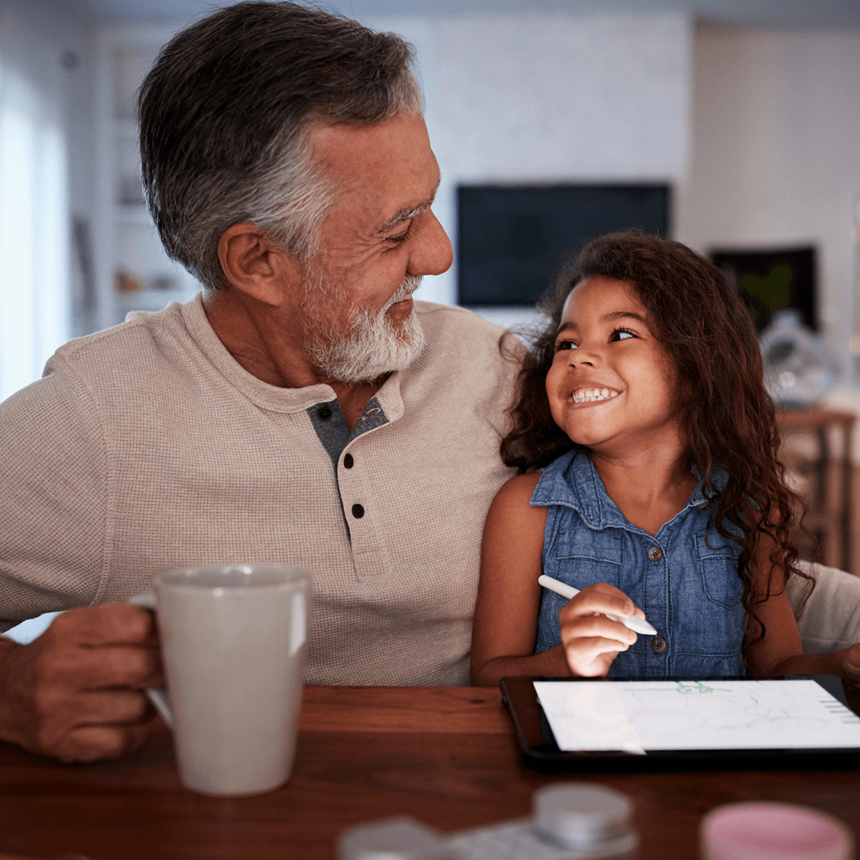 Grandpa coloring with a little girl.