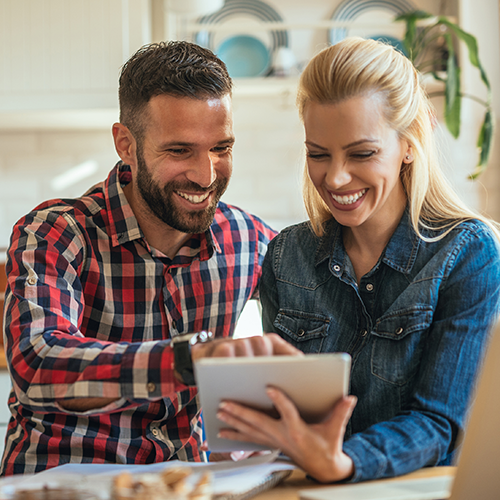 Man and woman reviewing account options on a tablet.