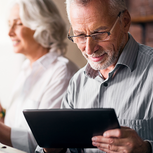 Grandpa looking at his retirement accounts on a tablet.